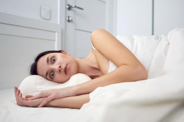 白いtシャツを着た女性の不眠症がベッドに横たわっていて、枕が部屋の毛布の下にあります