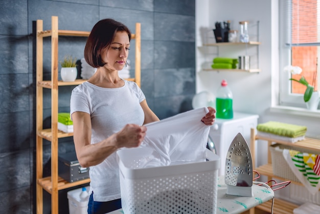 Woman inspecting clothes in basket at laundry room
