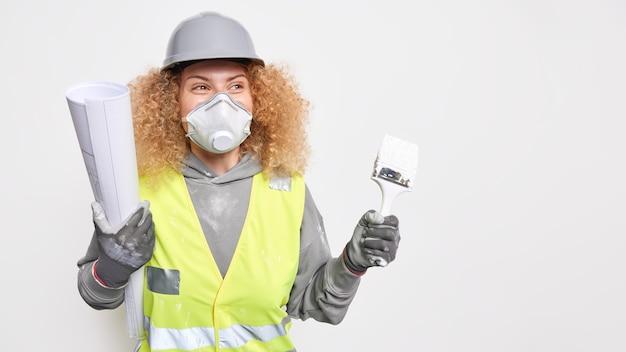女性の検査官が建設現場にやって来て、新しい建物のアイデアを提示します保護呼吸器のヘルメットを着用し、反射ベストは青写真とペイントブラシを保持します