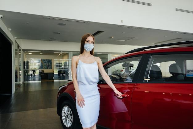 Женщина в маске осматривает новую машину в автосалоне во время пандемии.