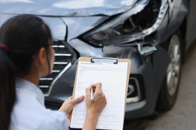 여성 보험 대리인은 교통 사고 검사 후 자동차 손상에 대한 보험 양식을 작성합니다