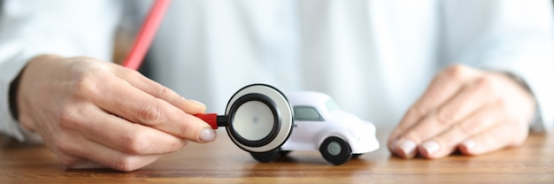 장난감 자동차 근접 촬영에 청진기로 듣는 여성 보험 대리인