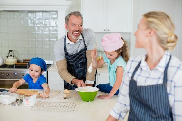 Женщина общается с мужчиной во время работы на кухне