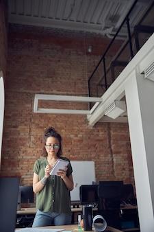 펜과 노트북을 들고 지저분한 머리를 가진 평상복을 입은 여성 인테리어 디자이너 또는 건축가