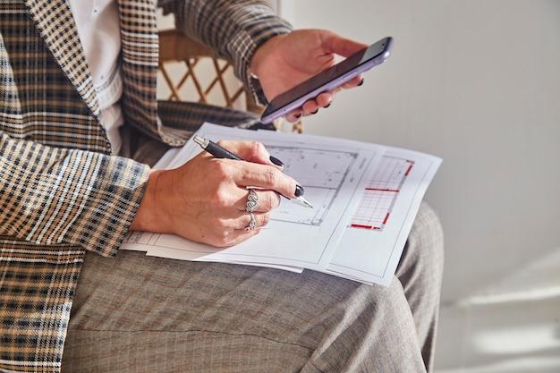새로운 프로젝트에 대한 내부 계획을 가진 여성 인테리어 디자이너는 그녀의 손에 펜을 보유하고 있습니다.