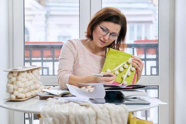 サンプルとオフィスのテーブルで働く女性のインテリアデザイナー