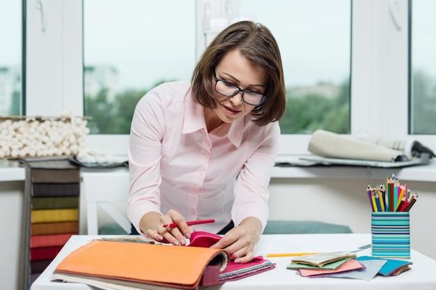 女性のインテリアデザイナー、生地のサンプルで動作します