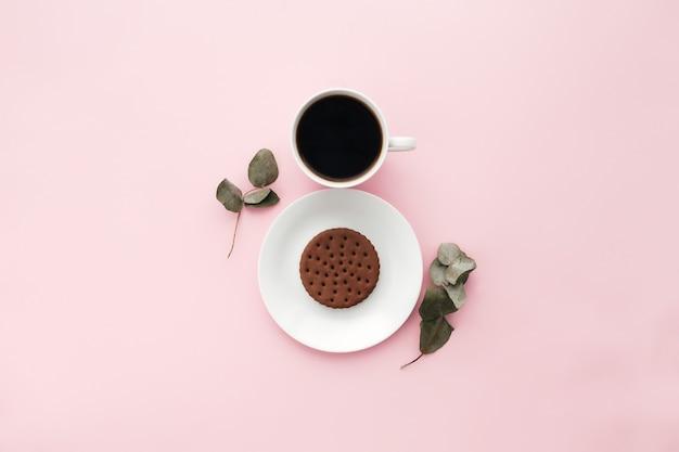 Концепция международного дня женщины, кофейная чашка, тарелка, печенье, ветка, листья эвкалипта на розовом фоне. фото высокого качества