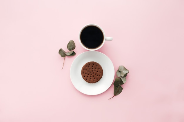 Woman international day concept, coffee cup, plate, cookie, branch, eucalyptus leaves on pink background. high quality photo