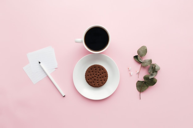 Концепция международного дня женщины, кофейная чашка, тарелка, печенье, ветка, примечания, ручка, листья эвкалипта на розовом фоне. фото высокого качества