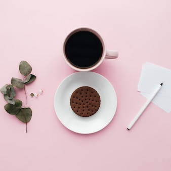 여자 국제의 날 개념, 커피 컵, 접시, 쿠키, 지점, 노트, 펜, 유칼립투스 분홍색 배경에 나뭇잎. 고품질 사진