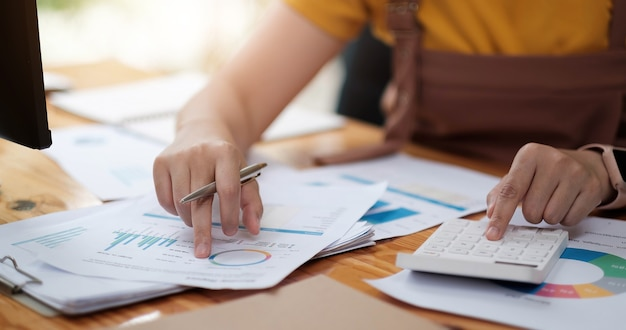 Woman investment consultant analyzing company annual financial report balance sheet statement working with documents graphs.