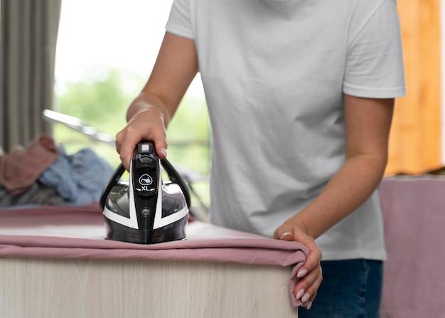 Женщина гладит одежду после сушки дома