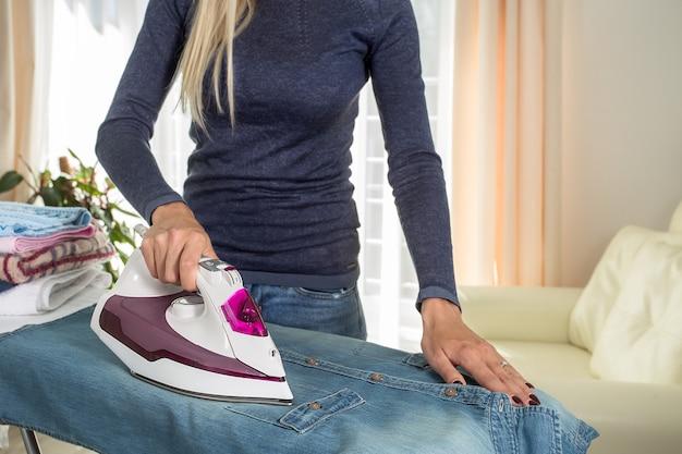 Женщина гладит одежду на борту дома закройте женские руки, гладящие синюю хлопковую рубашку на гладильной доске в домашнем интерьере. клининговые услуги, домохозяйка. место для текста