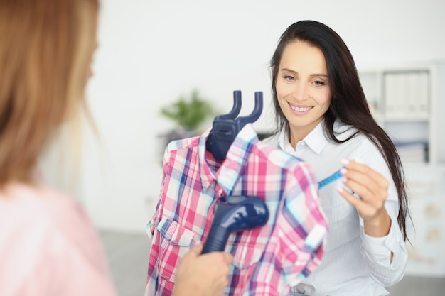 Woman ironing shirt with steamer at home closeup. dry cleaning clothes concept