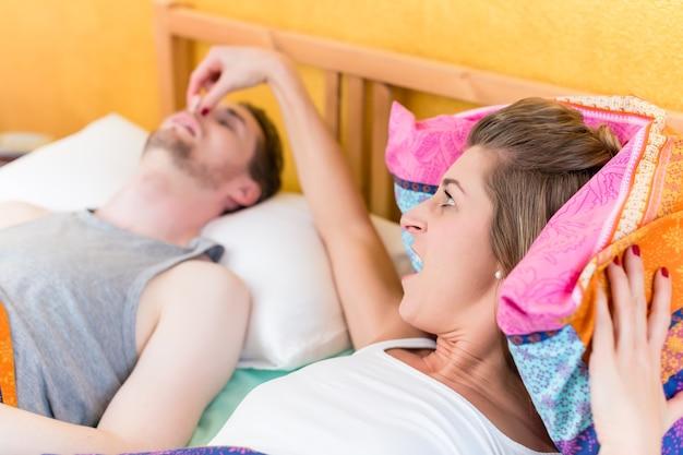 여자는 화가 나서 침대에서 코골이 파트너의 코를 잡고 있습니다.