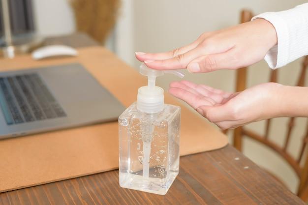 여자는 책상에 손에 소독제 젤을 적용 프리미엄 사진