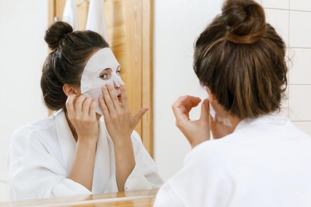 여자는 그녀의 얼굴에 시트 마스크를 적용
