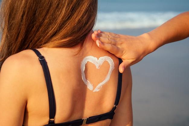 여자는 해변에서 그녀를 다시 수영복에 여자에게 자외선 차단제 크림을 적용