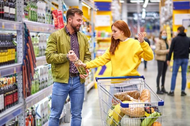 Женщина спорит с мужем алкоголиком в магазине в алкогольном отделе, шоппинге, концепции алкоголя