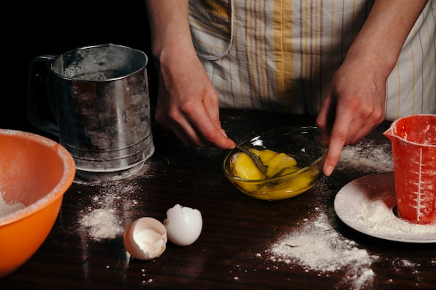 A woman is beating eggs in a bowl.