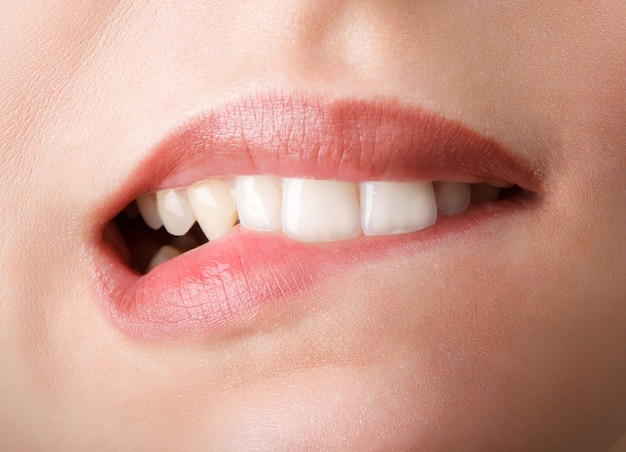 Woman is biting her red lips by teeth