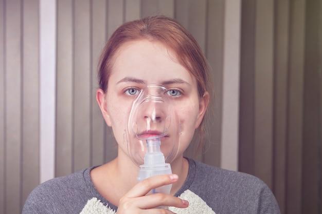 여성은 만성 폐쇄성 폐 질환을 앓고 있기 때문에 분무기 마스크의 도움으로 숨을 쉬고 있습니다.