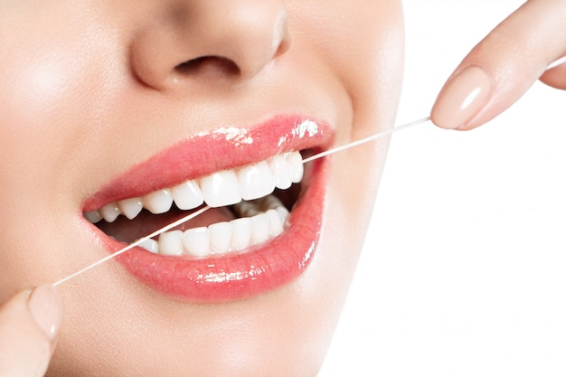 A woman is brushing her teeth using dental floss.