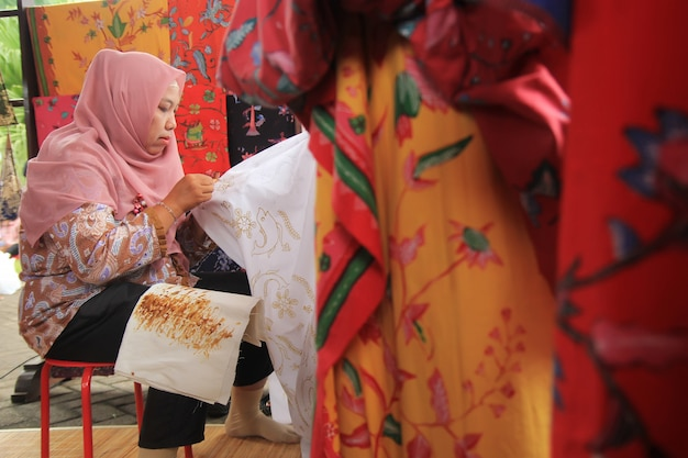 A woman is busy making batik using traditional canting in surabaya