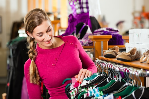 Woman is buying tracht or dirndl in a shop