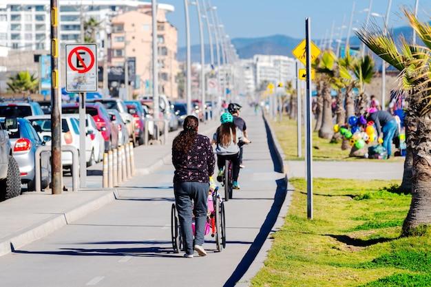 女性はビーチの背面図で障害者と車椅子を運んでいます