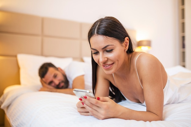 Woman is chatting using a smartphone while her boyfriend is bored in bed