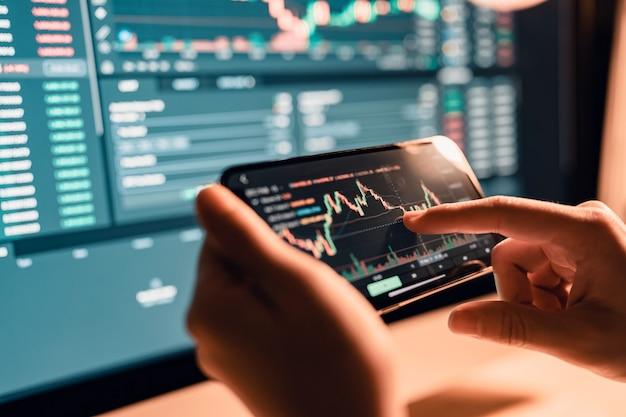 Женщина проверяет график цен на биткойны на цифровой бирже на смартфоне