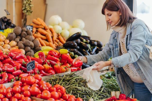 女性は食品市場で果物や野菜を選びます。ショッピング用の再利用可能なエコバッグ。持続可能なライフスタイル。環境にやさしいコンセプト。