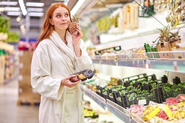 여자는 목욕 가운을 입고 저장소에 신선한 야채와 과일을 선택합니다. 식료품 슈퍼마켓에서 음식을 구입하는 젊은 여자