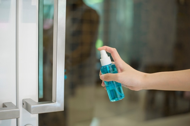 Woman is cleaning door handle with alcohol spray