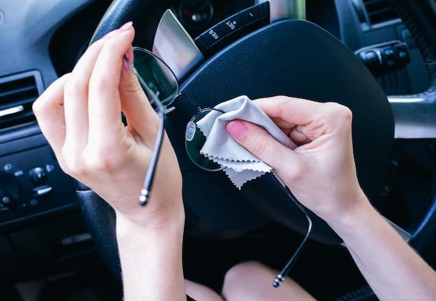 여자는 바퀴 뒤에 그녀의 안경을 청소입니다. 차를 운전하는 소녀.