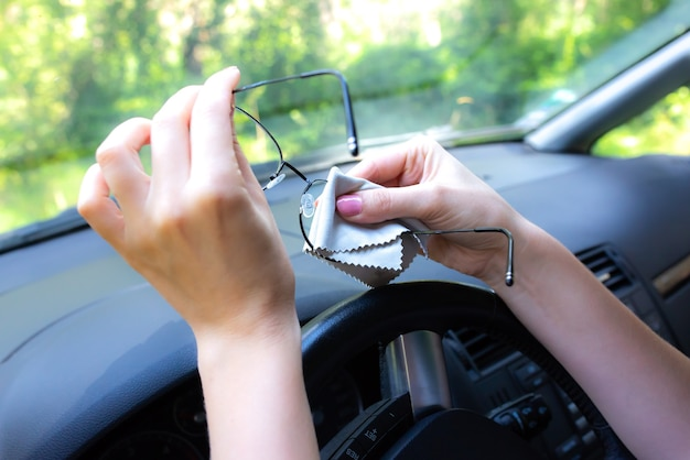 Woman is cleaning her glasses behind the wheel. girl driving a car.