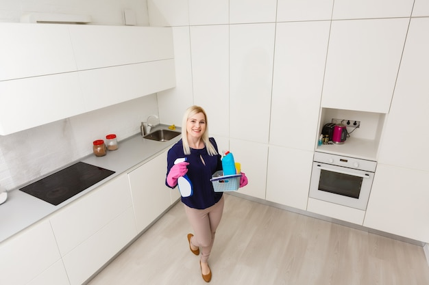A woman is cleaning the kitchen. she is looking away from the camera. horizontally framed shot.
