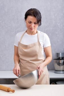 여자는 그녀의 손에 그릇으로 부엌에서 요리입니다. 수직 프레임.