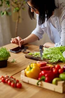 女性は自宅の台所で料理をし、デジタル タブレットやスマートホンを使い、レシピ、健康食品のコンセプト、ビーガン、ダイエットを探している。