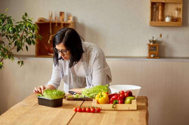 여자는 디지털 태블릿을 사용하여 집에서 부엌에서 요리