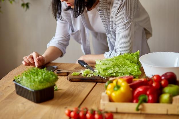 女性はデジタルタブレットを使用して、自宅のキッチンで料理をしています