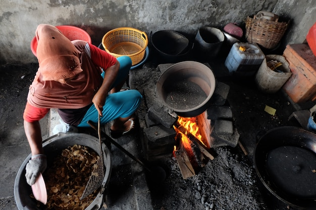 A woman is cooking using a traditional stove