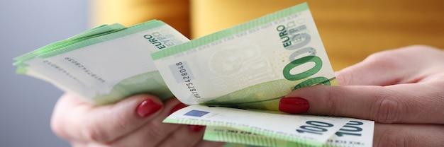 Женщина считает банкноты в сто евро. концепция расчета заработной платы