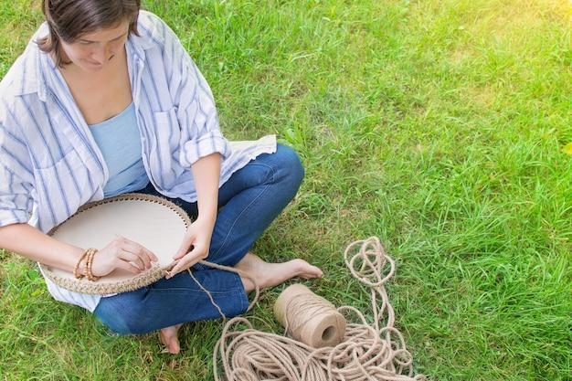 Женщина вяжет на траве корзину из толстого шнура из экологически чистых материалов.