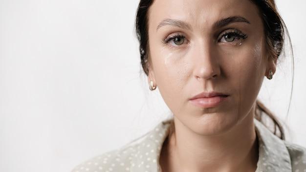 여자는 흰색 배경 근접 촬영에 그녀의 얼굴에 눈물을 가진 여자의 눈물 눈물 초상화를 운다