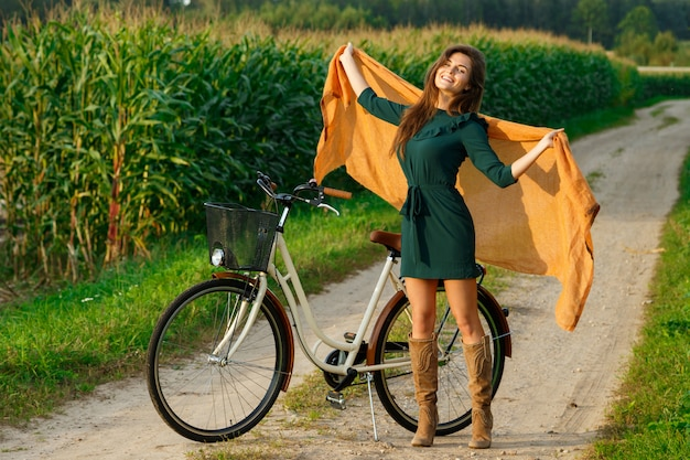 Woman is cycling by the country road in the cornfield