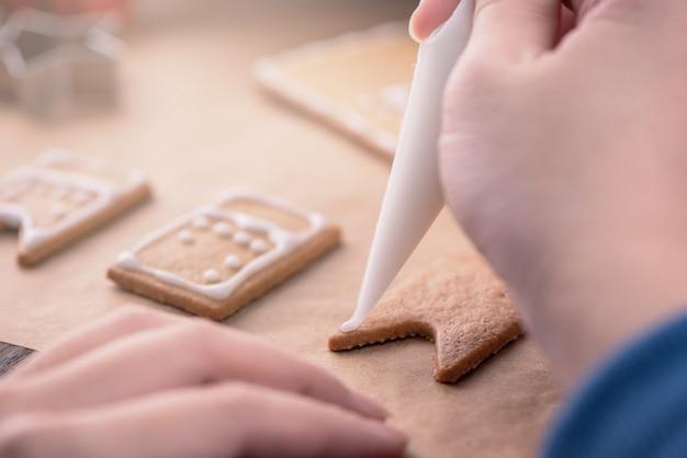 女性は、木製のテーブルの背景に白いフロスティングアイシングクリームのトッピング、キッチンで紙を焼く、クローズアップ、マクロでジンジャーブレッドクッキーの家を飾っています。