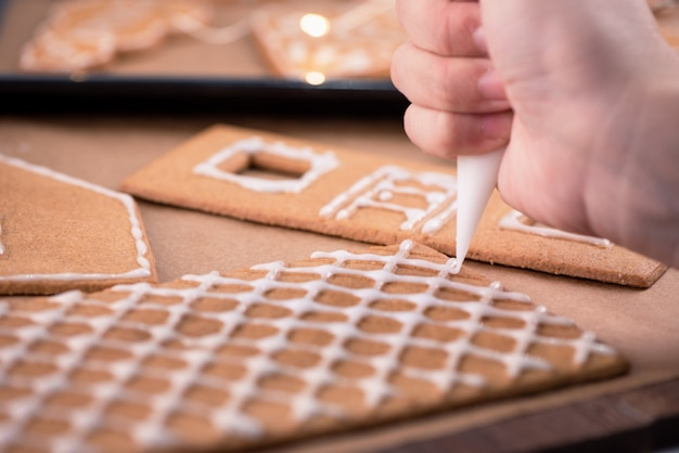 Woman is decorating gingerbread cookies house with white frosting icing cream topping on wooden table background, baking paper in kitchen, close up, macro.